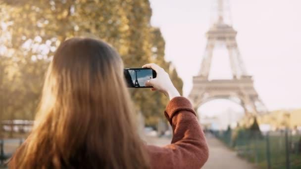 Zadní pohled na mladé dospívající samice pomocí smartphone pro fotografování Eiffelovu věž v Paříži.