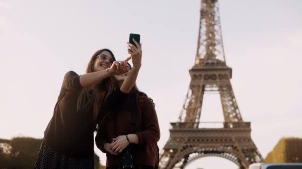 Dvě krásné cestování ženské pořizování fotografií na smartphone poblíž Eiffelovu věž v Paříži v slunečný den.
