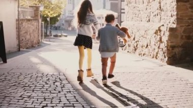 Two little run together holding hands. Slow motion. Back view. Girl and boy chasing pigeon on a bright sunny day. Unity.