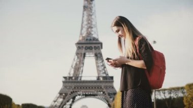 Young beautiful woman with backpack standing near the Eiffel tower and using the smartphone, browsing the Internet.