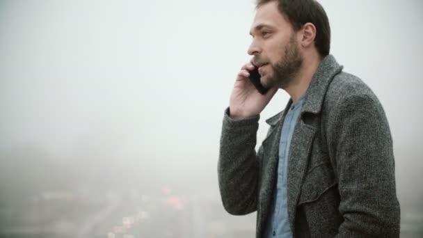 Mladý muž stojící poblíž Eiffelova věž v Paříži v mlhavé ráno. Muž s někým mluvit na mobilním telefonu.
