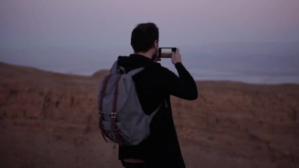 Man takes photos of amazing violet sky panorama. Slow motion. Excited tourist makes smartphone video of dusk mountains.