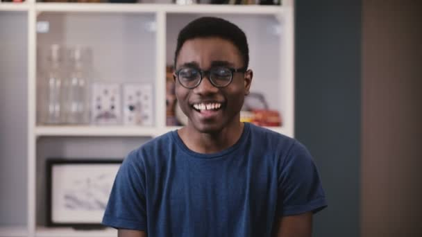 Happy African American businessman looks at camera. Handsome black young guy in glasses smiling joyfully. Student. 4K