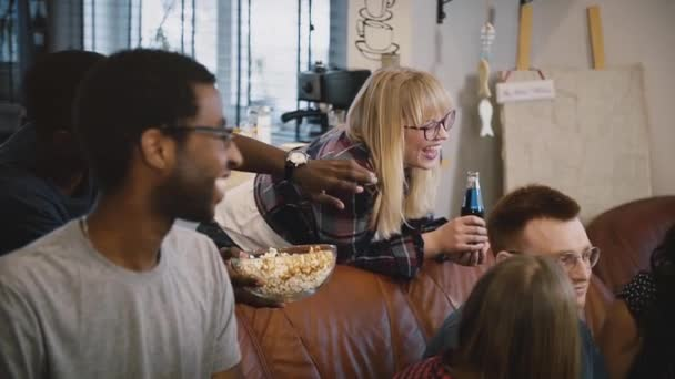 Friends sit together, watch funny movie on TV. Multi-ethnic group watching sports, discussing and chatting joyfully.