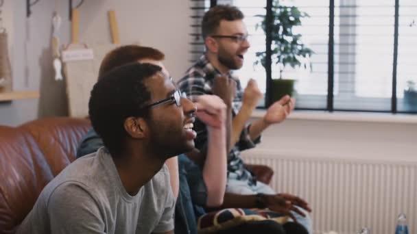 Multi etnické přátel sledovat sportovní přenosy v televizi. Zpomalený pohyb. Emocionální fotbaloví fanoušci slaví vítězství společně. Boční pohled.