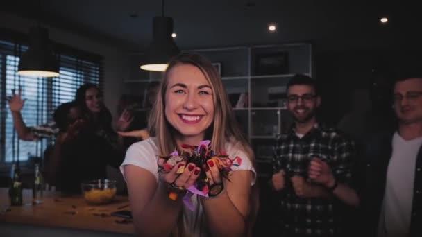 Krásné Evropské dívka foukání konfety. Happy vzrušená paní fouká třpytky na multi etnické strany. Taneční oslavu