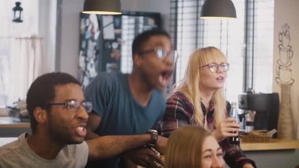 Více etnických přátel sledování sportovních přenosů v televizi. Zpomalený pohyb. Fotbaloví fanoušci slaví vítězství s občerstvením a nápoji. Emoce