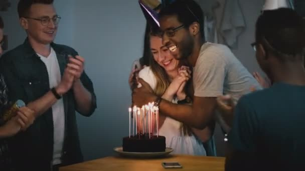 Pretty Caucasian girl holds birthday cake smiling. Multi ethnic friends in fun hats celebrate together and hug happy. 4K