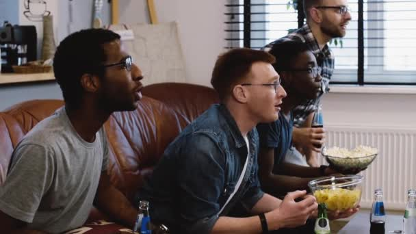 African American friends watch sports on TV. Slow motion. Fans celebrate goal excited on the couch with popcorn. Emotion