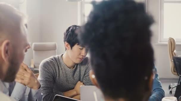 Gemischter ethnischer Herkunft Team Geschäftsideen diskutieren. Junge asiatische Mitarbeiter im Büro Teamarbeit brainstorming Meetup sprechen. 4k