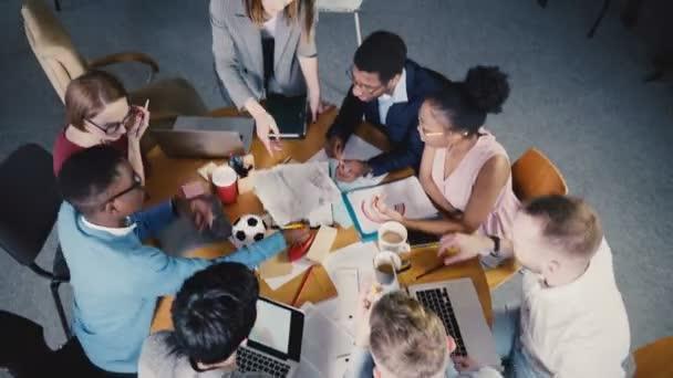 Draufsicht multiethnischen Kreativteam Brainstorming in trendigen modernen Coworking Büro. Chefin führt die Sitzung 4k