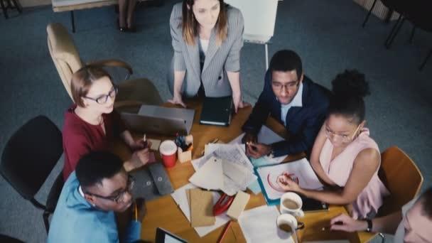Pohled shora týmovou práci na rozvoji společnosti úřadu. Mnohonárodnostní tvůrčího týmu diskutovat o trh s nemovitostmi v tabulce 4k
