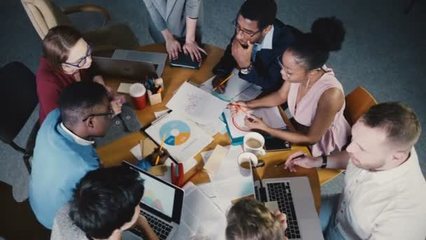 Frauenchefin leitet Team Office Meeting. Mischethnizität Kollegen betrachten Marktforschungsdaten Diagramme 4k.