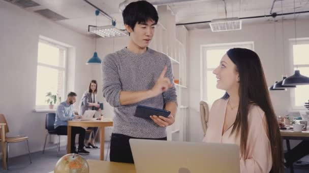 Multiethnic colleagues talk in modern office. Young happy Asian man discussing work with beautiful Caucasian girl 4K.
