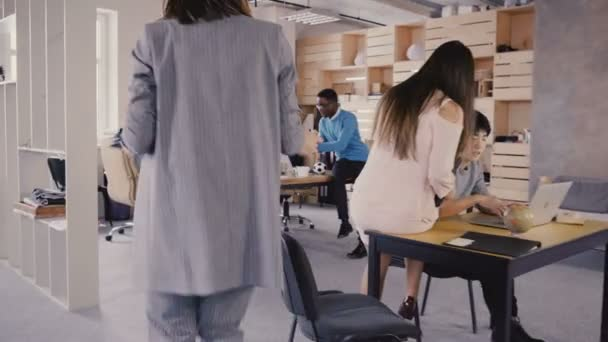 Camera follows businesswoman in office, moves on through trendy modern coworking. Happy multiethnic business people 4K.