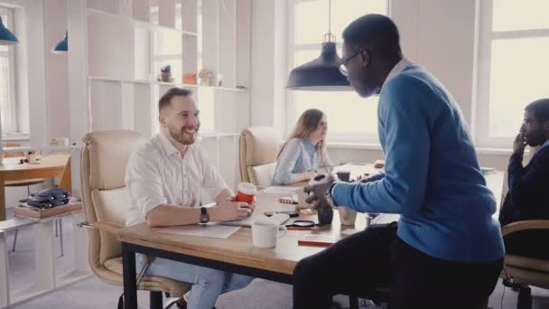Happy multiethnic colleagues talking in office. Young mixed race business partners enjoy casual office atmosphere 4K.