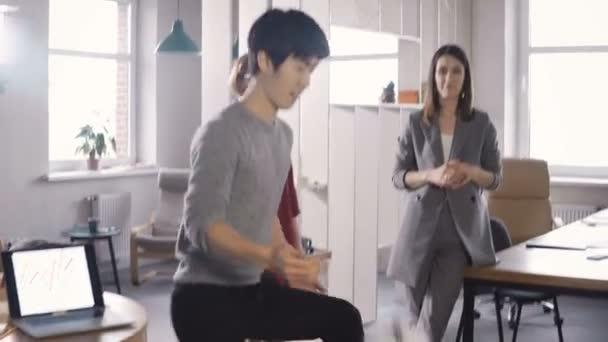 Happy asijské zaměstnanec žonglování fotbal v úřadu. Usmívající se mnohonárodnostní pracovníky slavit úspěch v podnikání v kruhu 4k