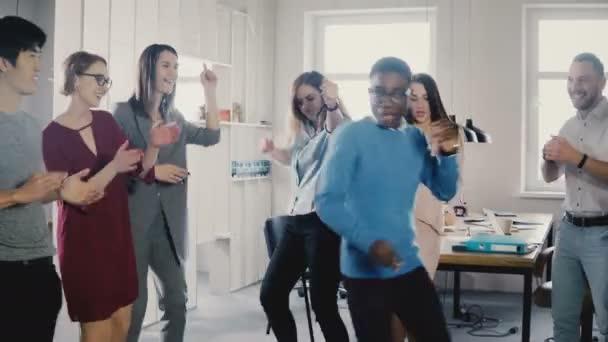 Happy americký podnikatel tanec. Příležitostné muž slaví vítězství a úspěch s kolegy Smíšené rasy 4k