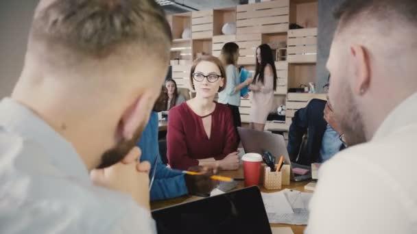 Tým debaty v moderní kanceláři módní podkroví. Mladí mnohonárodnostní kreativní usmívající se zaměstnanci firmy diskuse 4k.