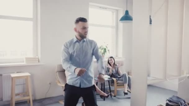 Funny crazy dancing businessman celebrating victory with excited multi-ethnic colleagues in modern light office 4K.