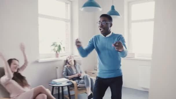 Šťastný americký podnikatel oslava povýšení zábavný taneční chůze. Úspěšný šéf v moderní kanceláři 4k
