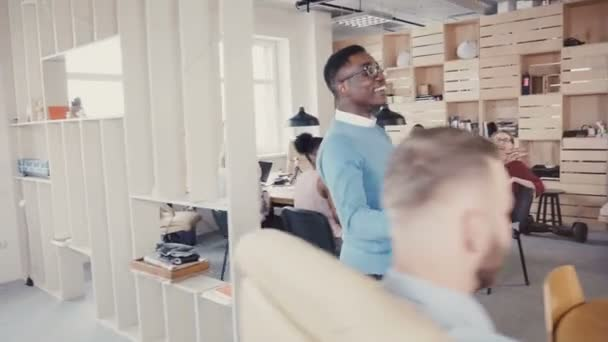 Happy African American man gives high fives to office colleagues. Celebrating business success with joyful dance 4K.