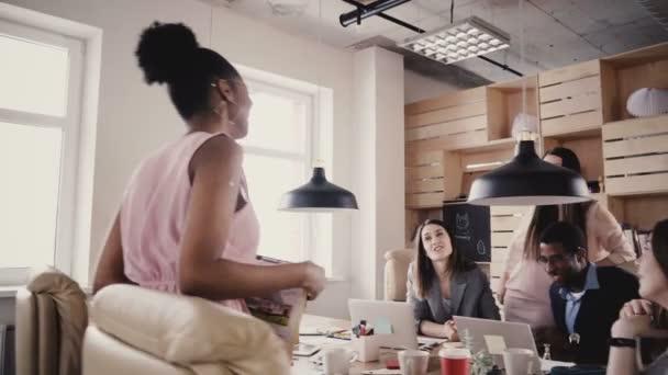 Happy African American female boss leading office team meeting. Multiethnic group brainstorming, generating ideas 4K.
