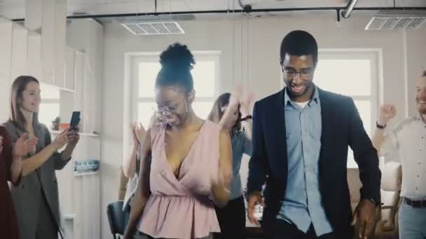African American male and female employees doing funny ethnic dance moves at office party with multiethnic colleagues 4K