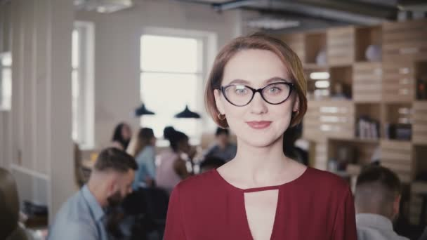 Happy confident European young businesswoman smiling at camera. Confident female boss posing in office background 4K.
