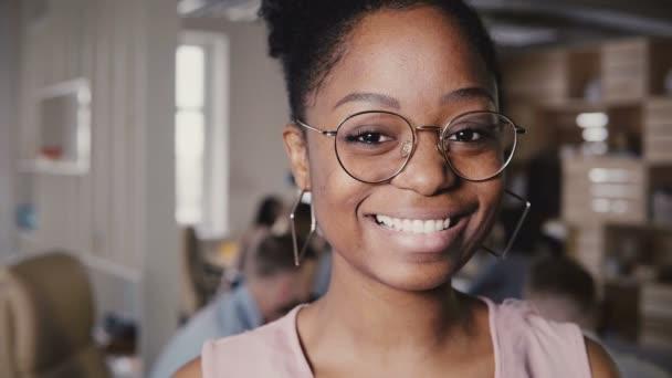 Krásné mladé afroamerické šťastné ženské vůdce v brýlích se usmívá na kameru v moderní kanceláři co-Working pozadí 4 k