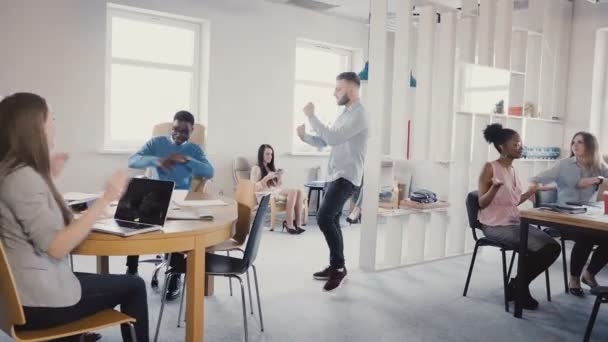 Young happy businessman doing victory dance, celebrating team success with mixed race employees in modern office 4K.