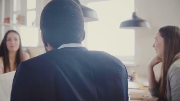 Mnohonárodnostní podnikatelů spolupracovat v moderní podkrovní kanceláři. Mladí šťastní kolegové usmívající se, diskutovat o projektu 4k