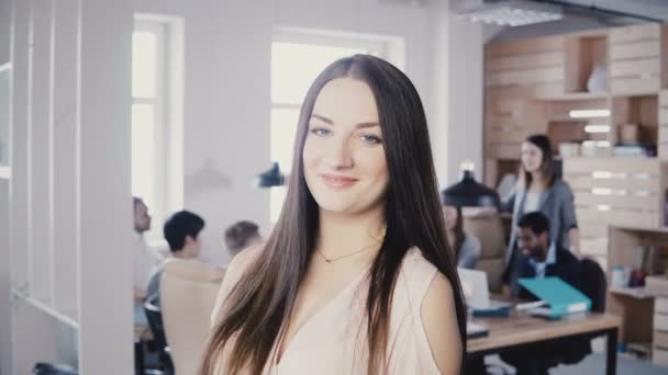 Happy confident European young female manager with long hair and amazing blue eyes smiling at camera in modern office 4K