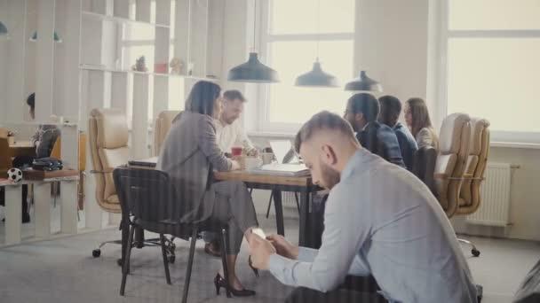 Dolly záběr mnohonárodnostní obchodních setkání v moderní kanceláři. Mladý úspěšný Evropský obchodník pomocí smartphonu 4k