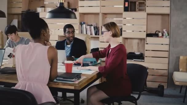 Female team leader guides employees in office. Confident businesswoman talking at multiethnic start-up team meeting 4K.