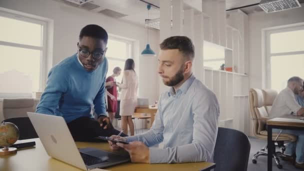 Two young multiethnic friends collaborate in stylish loft office, European female manager comes up to help them 4K.