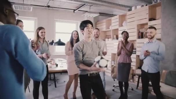 Asiat se snaží udržet fotbal na hlavu v úřadu. Happy smíšené etnického původu pracovníků hraje zábavné sportovní hry pomalý pohyb