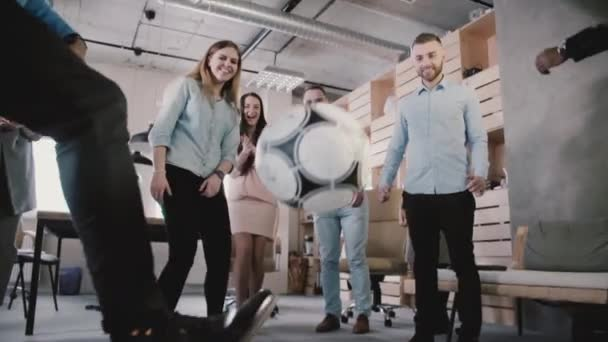 Close-up of male legs playing with football in office, slow motion low angle. Happy colleagues enjoy physical activity.