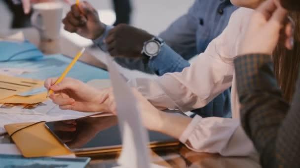Detailní záběr zaneprázdněn různorodí podnikatelé sedí za velkým kancelářským stolem se zařízeními a dokumenty spolupracující na setkání.