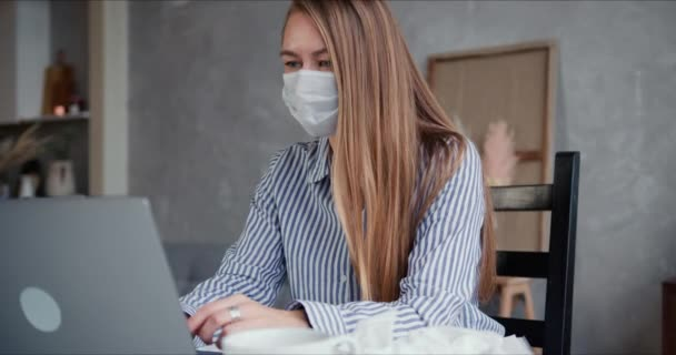 Beautiful young blonde doctor woman using laptop to work, consult people from home on self isolation wearing face mask.