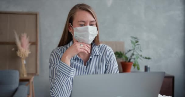 Young professional doctor woman using laptop to help and consult people from home online on quarantine wearing face mask