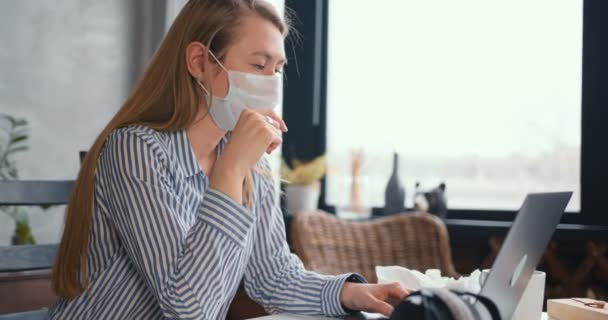 Young happy medical worker woman using laptop to work from home, consult people online on quarantine wearing face mask.