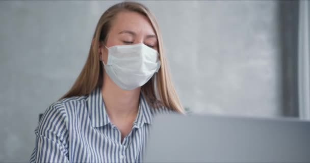 Young Caucasian doctor woman working from home online using laptop, consulting people on quarantine wearing face mask.