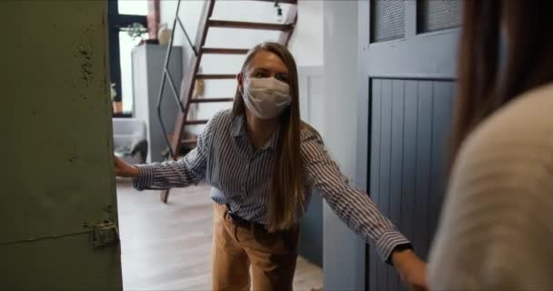Young Caucasian woman wearing mask opens apartment door to get delivery bags from courier on self isolation lockdown.