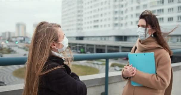 Zwei junge kaukasische Frauen mit Gesichtsmasken reden draußen auf der Straße der Stadt, beraten einen Arzt mit Klemmbrett.