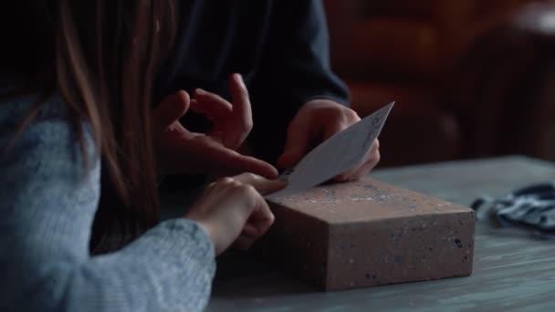Close-up fiatal romantikus pár unboxing ünnep meglepetés ajándék doboz szállítás otthon egy üdvözlő képeslap lassított felvétel