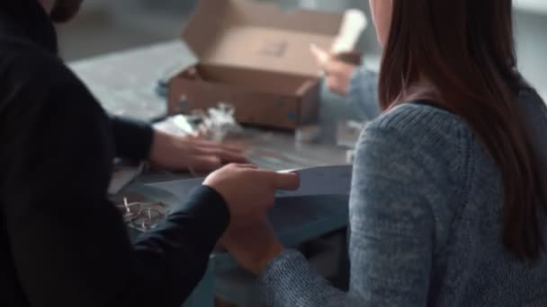 Rear view young happy romantic couple unpacking box with creative family boardgame to play together at home slow motion.