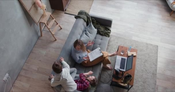 Self isolation. Top view tired mother trying to work from home using laptop, distracted by two noisy teenage children.