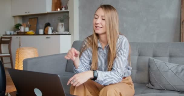 Business woman working from home. Happy young smiling blonde female tutor checks papers on laptop video conference call.
