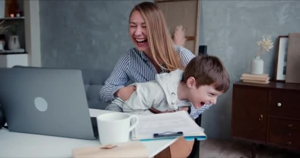 Family fun at home on quarantine. Young happy cheerful Caucasian mother and cute son laugh watching cartoons on laptop.